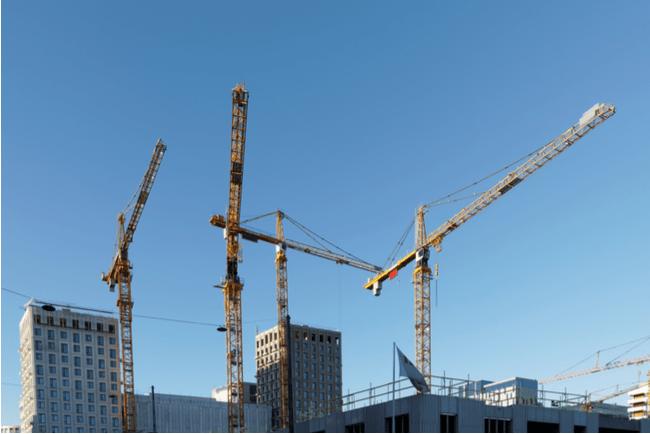 En bild på lyftkranar vid ett bygge
