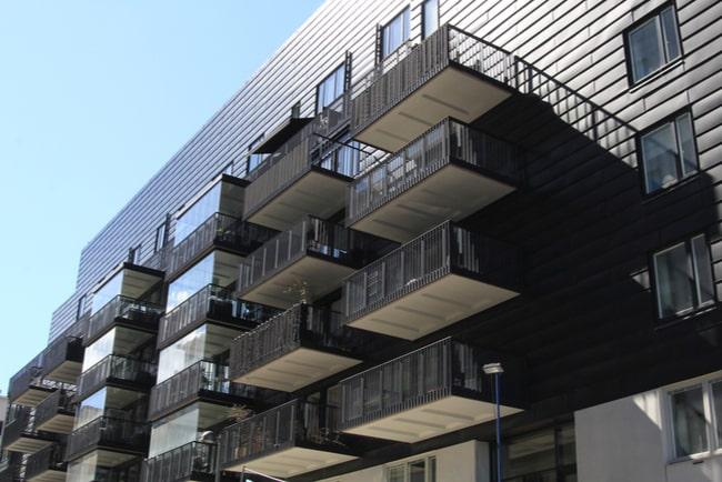 brunt nyproducerat flerbostadshus med många balkonger på varje våning