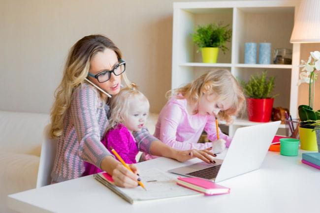 Ensamstående mamma med två barn. Mamman sitter vid skrivbord med ett barn bredvid sig och ett mindre barn i knät. Hon pratar i telefon och har en lapptop framför sig.