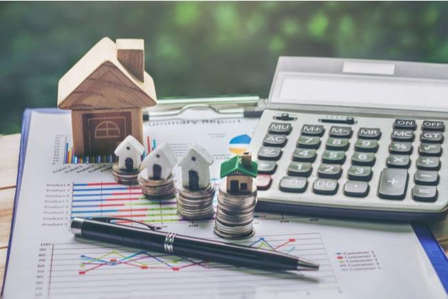 Miniatyrhus, myntstaplar, miniräknare penna och kalkylblad för att räkna på bolån