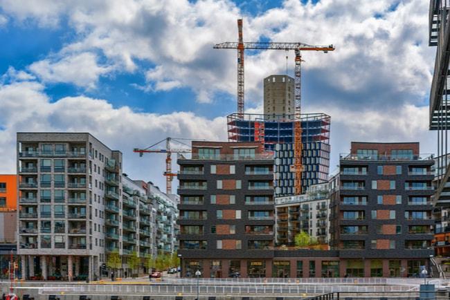 Nybyggda lägenheter i Hammarby sjöstad och en lyftkran i bakgrunden.