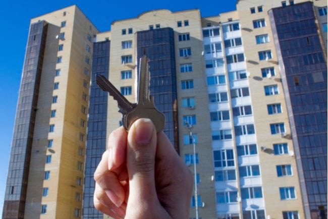 Hand som håller upp två nycklar till en bostad och höghus i bakgrunden
