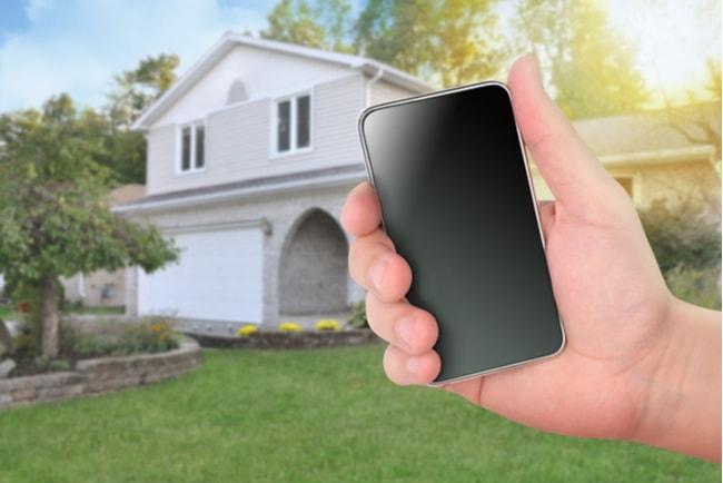 Hand som håller i en smartphone framför ett hus