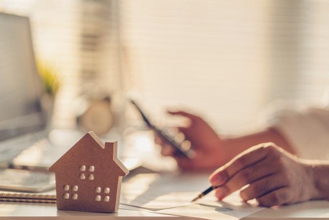 En vänsterhand som håller i en penna över ett papper och en högerhand som håller i en miniräknare. Framför vänsterhanden står ett miniatyrhus i trä.
