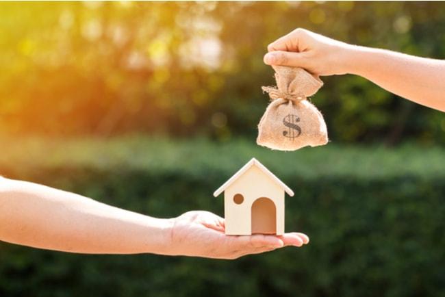 man och kvinna håller penningpåse och husmodell mot varandra