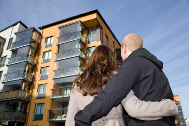 ungt par tittar upp mot bostadshus