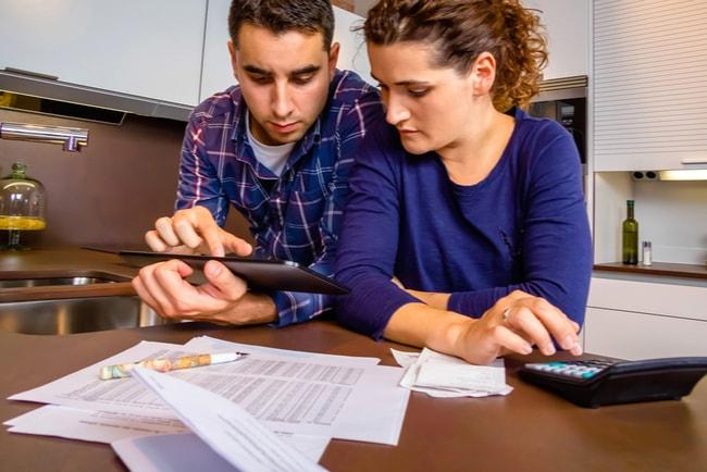 ungt par sitter vid bord och betalar räkningar