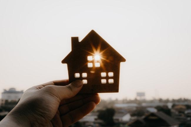 hand håller upp miniatyrhus med solen som lyser genom fönstret