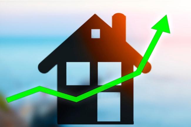 graf på tillväxt på bostadsmarknaden med hus i bakgrunden och grön pil i förgrunden