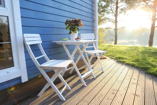 utemöbler står på veranda med solen strålande mellan träden i bakgrunden