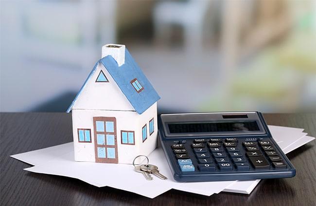 minihus står på papper bredvid en miniräknare