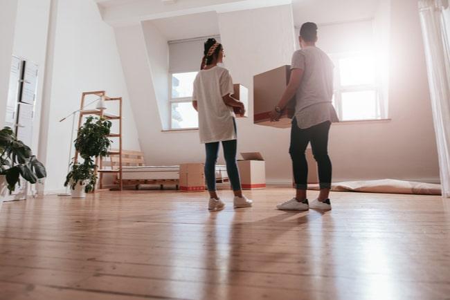 ungt par står i lägenhet med flyttkartonger