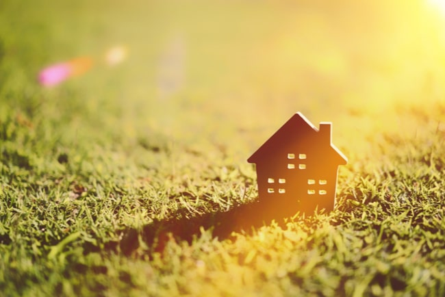 miniatyrhus står på gräsmatta med solljus i bakgrunden