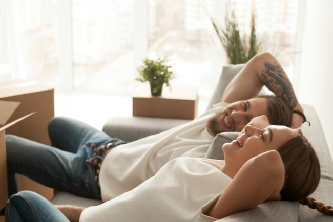 ungt par sitter i soffan och skrattar omgivna av flyttkartonger