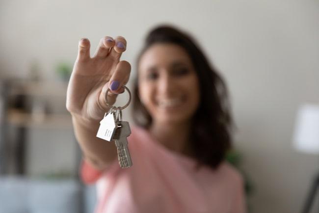 Leende kvinna håller upp nycklar.