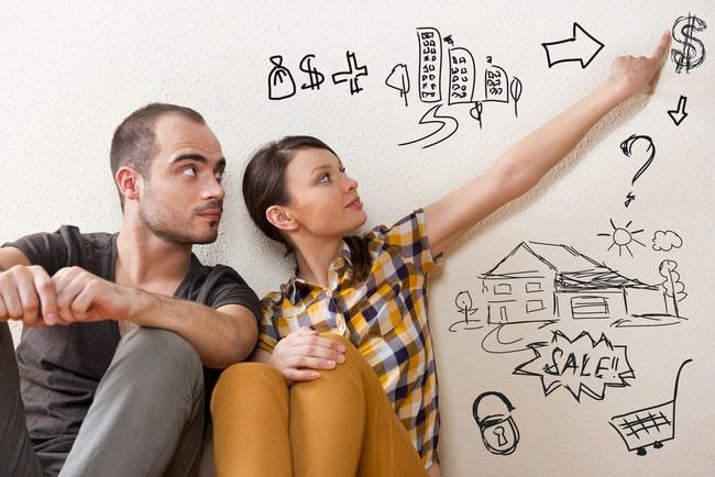 Ungt par sitter vid en vägg och planerar husköp.