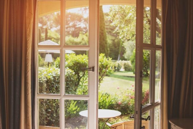 Öppen altandörr som leder ut mot trädgård.