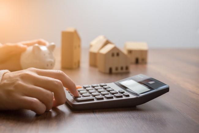 Person knappar på miniräknare och håller i spargris bredvid hus i miniatyr.