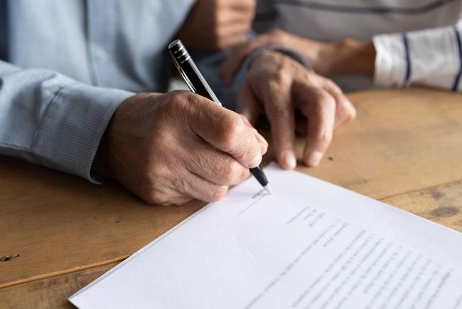 Äldre par skriver på kontrakt.