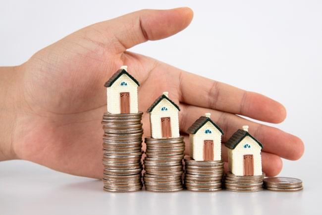 myntstaplar med hus på och en hand bakom som visar att staplarna minskar