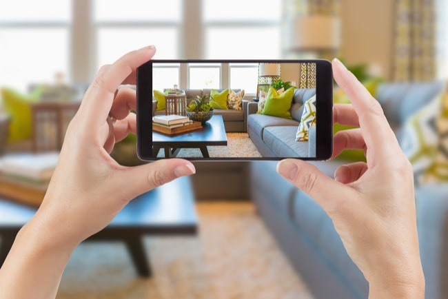 kvinna tittar på ett rum genom sin mobiltelefon