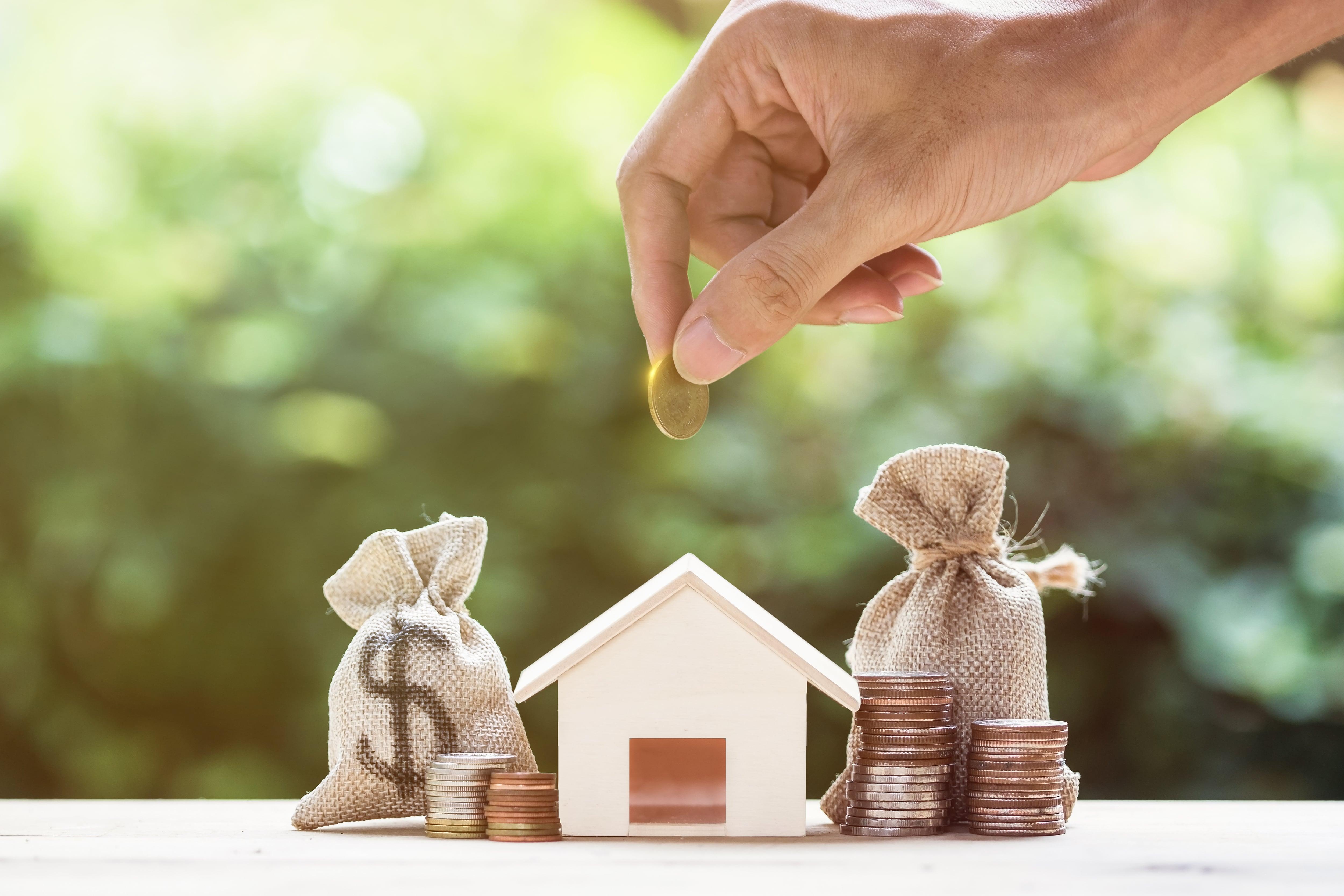 Hand som tänker stoppa mynt i ett hus som en sparbössa och flera myntstaplar runt huset.