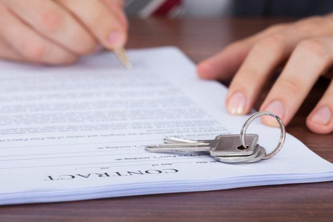 person signerar kontrakt med nycklar på