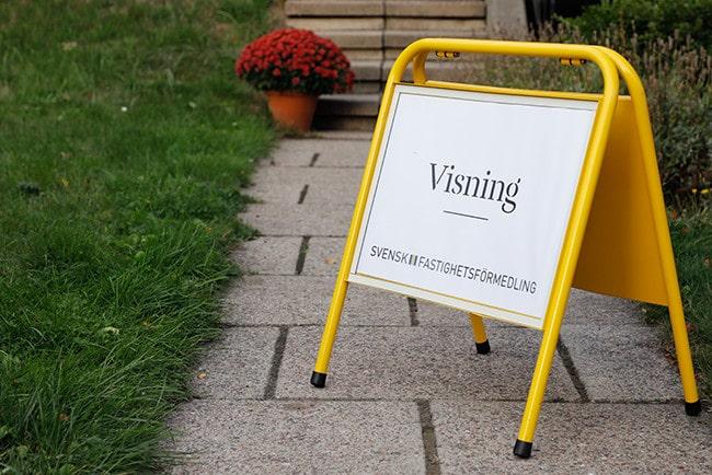 Visningsskylt från svensk fastighetsförmedling som står på en gång mot ett hus
