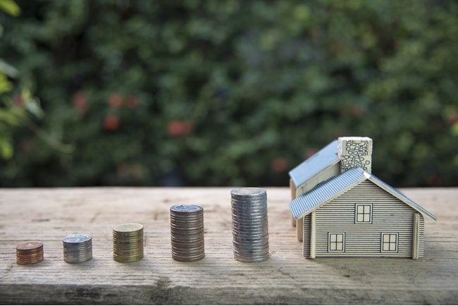 Fem myntstaplar som blir större och ett litet grått miniatyrhus på ett bord och grön bakgrund