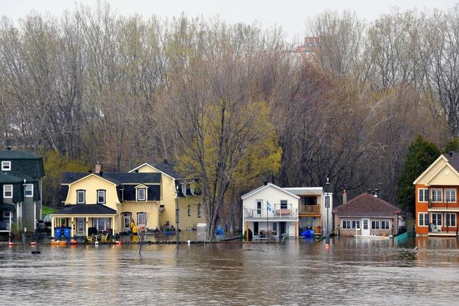 Flod som har svämmat över och når upp till husen