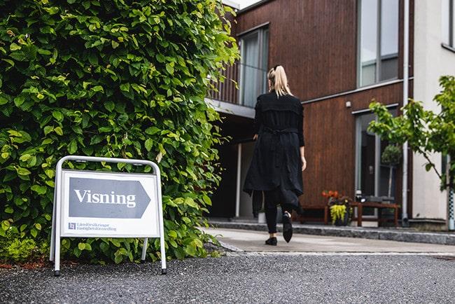 Kvinna sett bakifrån klädd i svarta kläder och skor som är på väg till en lägenhetsvisning.