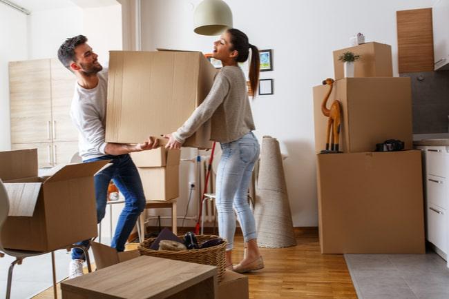 Ungt par bär in en flyttkartong tillsammans i deras nya bostad.