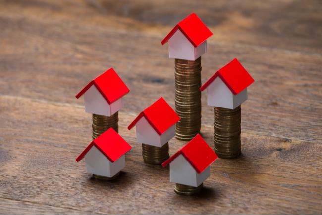 husmodeller på staplar av mynt i olika höjd