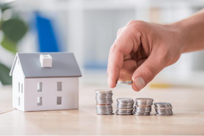 Vitt miniatyrhus med grått tak med penningstaplar i olika storlekar och hand som lägger ett mynt på en av staplarna.