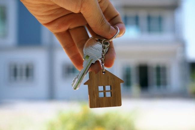 Hand som håller i en nyckelknippa med ett miniatyrhus och husnyckel med ett hus i bakgrunden.