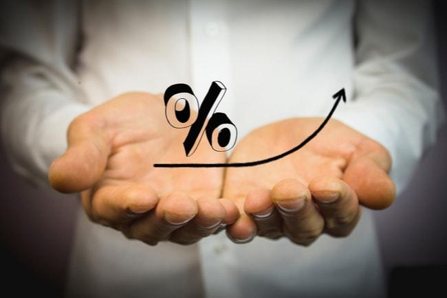 två händer som hålls ihop med handflatorna uppåt procenttecken och en pil som visar att räntan förändras