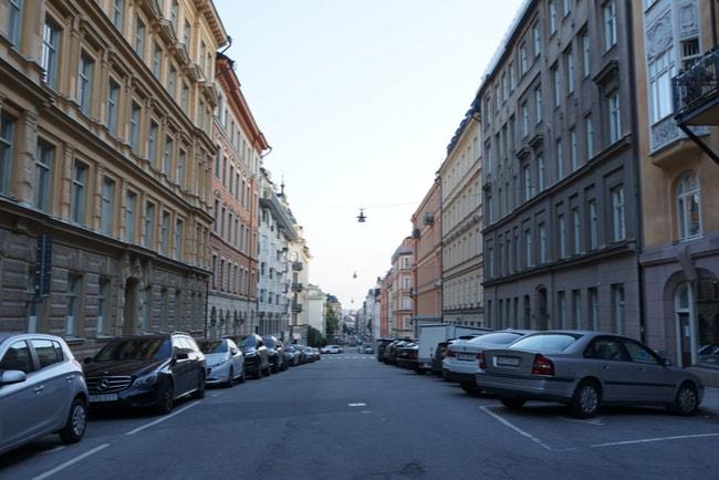 Gata i centrala Stockholm med lägenhetshus på vardera sida och bilar som står parkerade längs gatan.
