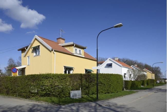 Villagata i förort till Stockholm med en gul villa och en vit villa på tomter som omgärdas av en grön häck.