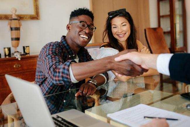 Ungt par, en man och en kvinna, skakar hand med bankman.