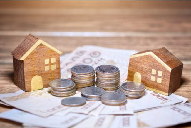 husprototyper på bord med mynt och sedlar